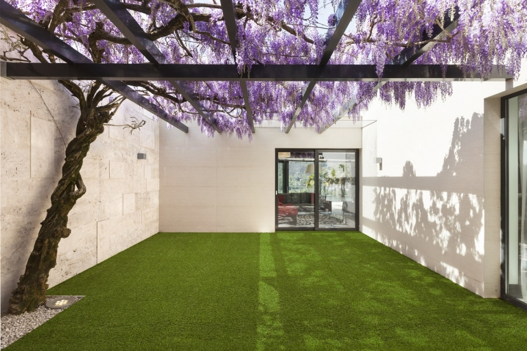 A house with a courtyard covered in artificial turf
