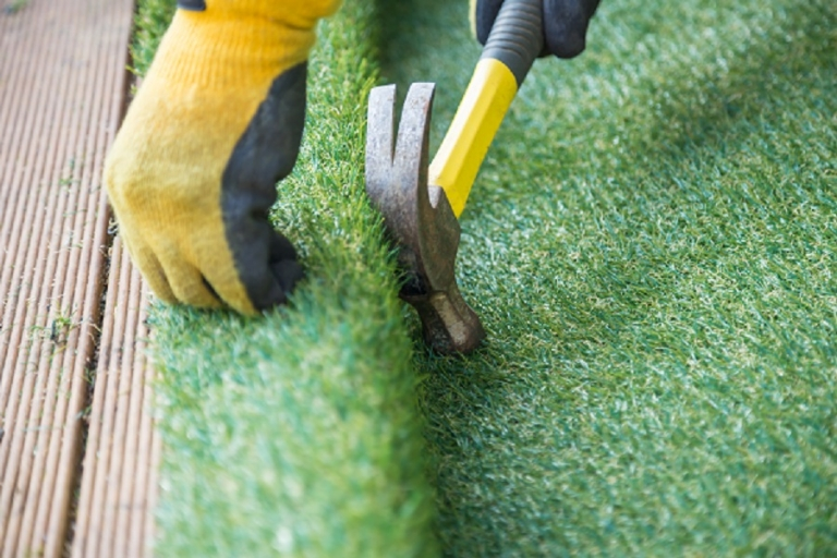 Hammering down artificial turf onto wooden decking