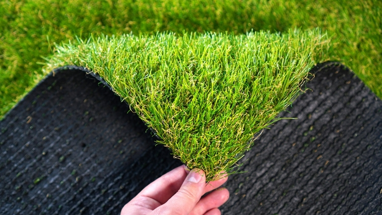 Hand folding down the corner of a piece of artificial grass