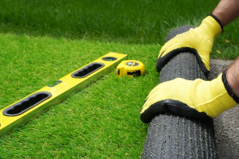 Rolling out artificial turf onto a concrete base